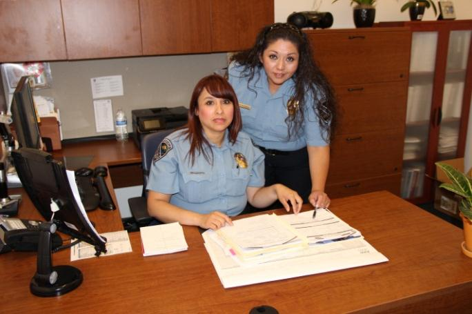 Two police officers sitting at a wooden desk.