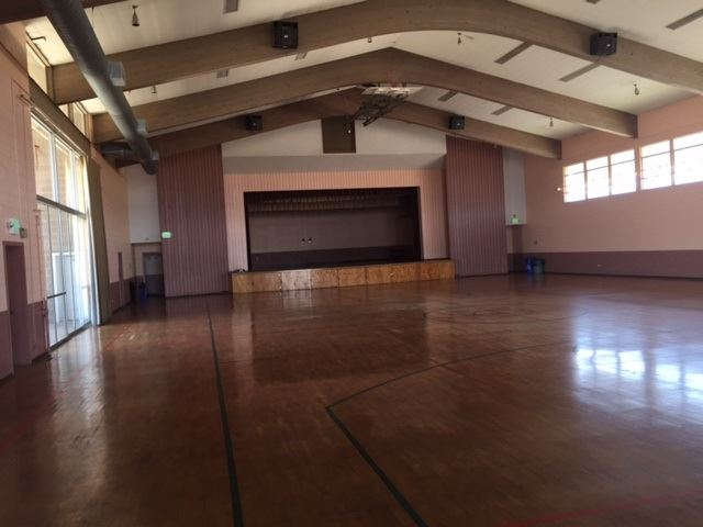 The inside of Memorial Hall. A large room with a basketball court floor and a stage at the end.