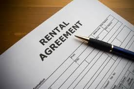 A rental agreement and a pen on a desk.